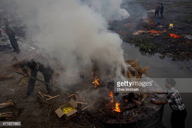 People tend to the cremation of an earthquake victim at Pashupatinah Temple on April 29, 2015 in Kathmandu, Nepal. A major 7.8 earthquake hit...