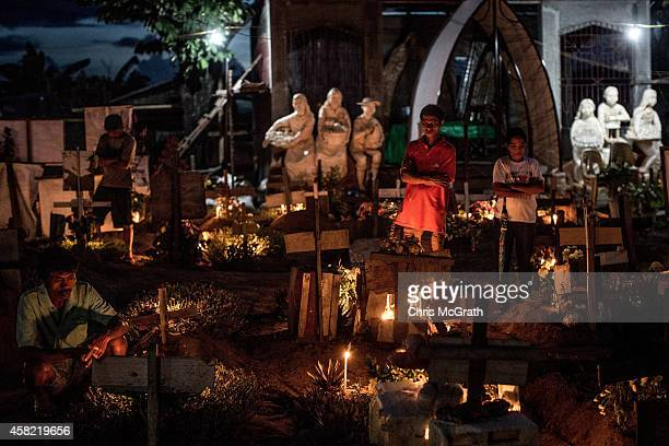 TACLOBAN LEYTE PHILIPPINES NOVEMBER 01 People tend to the grave of a loved one killed in the aftermath of Typhoon Haiyan at the mass grave site on...
