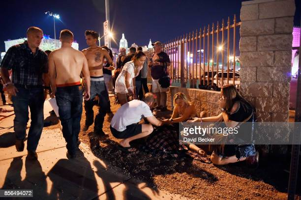 People tend to the wounded outside the Route 91 Harvest Country music festival grounds after an apparent shooting on October 1 2017 in Las Vegas...