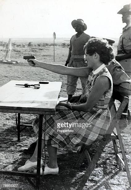 circa 1952 near Nairobi Kenya A white housewife is given instruction on how to use a handgun to protect herself during the Mau Mau uprising when the...