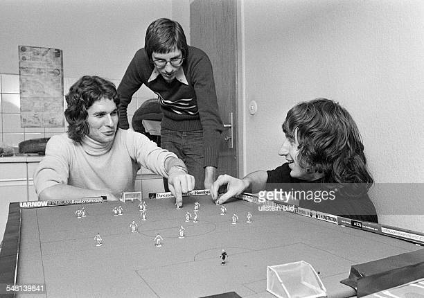 people three young men playing table football freetime hobby longhaired aged 20 to 25 years Juergen Harald Peter