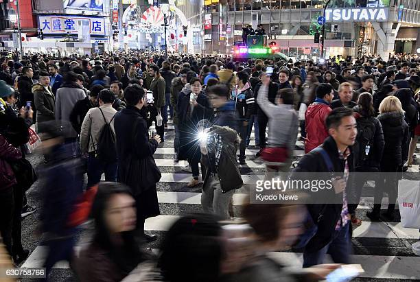 People throng Tokyo's Shibuya crossing on the night of Dec 31 2016 Police made an area around the crossing offlimit to cars from late night on Dec 31...