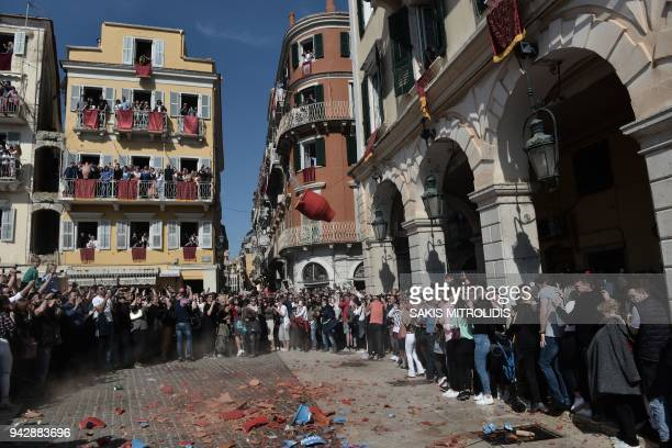 People throw clay pots filled with water off balconies as they take part in a custom at Corfu island that takes place on Holy Saturday morning on...