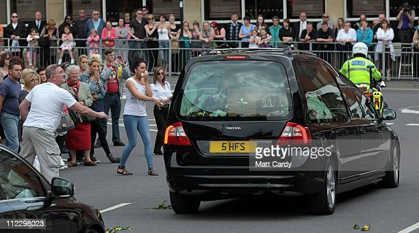 People throw flowers as wellwishers line the streets to pay their final respects as the hearse carrying the coffin of murdered nightclubber Sian...