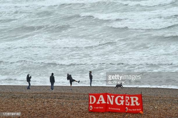 People throw pebbles and their dog runs near to a warning sign advising against swimming as a rough sea pounds the beach at Brighton on the south...