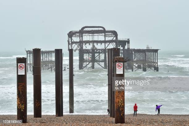 People throw pebbles into the water as a rough sea surrounds the derelict west pier in Brighton on the south coast of England on August 25, 2020. -...
