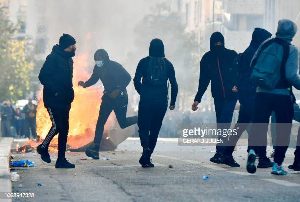 People throw projectiles as they stand near a burning garbage on December 6 2018 in Marseille southern France on the sideline of a demonstration of...