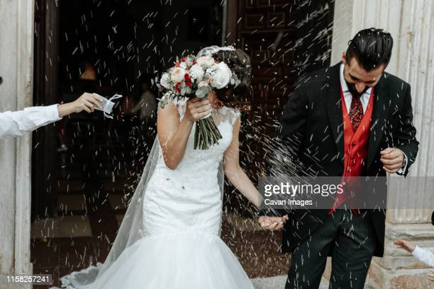 people throw rice on newlyweds walking out of the church - boda fotografías e imágenes de stock