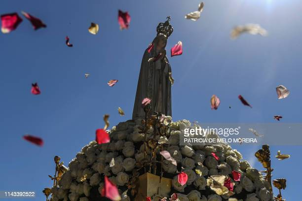 TOPSHOT People throw rose petals at the statue of Our Lady Fatima during a procession at the Fatima shrine in Fatima central Portugal on May 13 2019...
