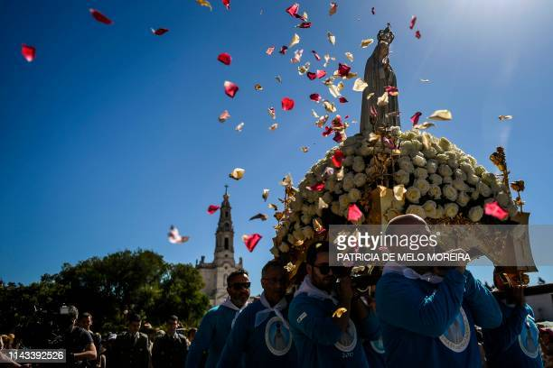 People throw rose petals at the statue of Our Lady Fatima during a procession at the Fatima shrine in Fatima central Portugal on May 13 2019...