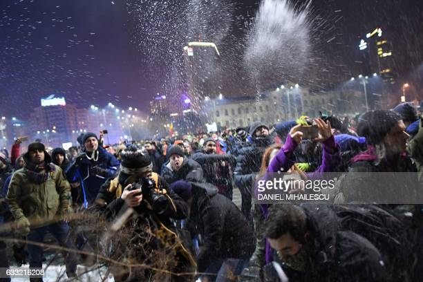People throw snow toward jandarmes protecting government headquarters as they demonstrate in front of Romanian Government headquarters against...