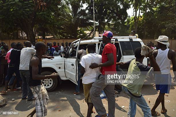 People throw stone at a car transporting two children of an exSeleka colonel at the 'UN crossroad'' on January 12 2014 In Bangui Rival militiamen on...
