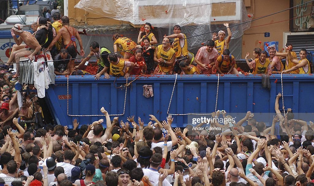People throw tomatoes from a lorry during the 'Tomatina' on August 31, 2005 in Bunyol, Valencia, Spain. The origins of the Tomatina are unknown, however fifty years on and 45,000 people flood to the region to pelt each other with over over 100.000 kilograms of Spain's finest tomatoes.