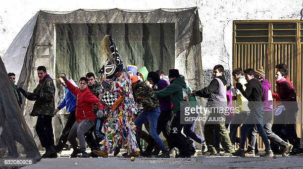 People throw turnips at a man representing the Jarrampla beating his drum and sporting a costume covered in multicoloured ribbons and his face hidden...