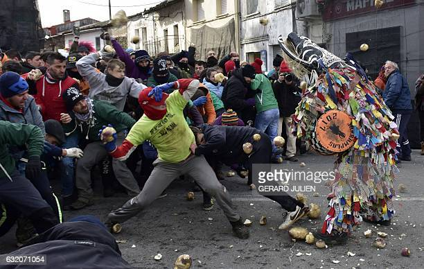 People throw turnips at a man representing the Jarrampla sporting a costume covered in multicoloured ribbons and his face hidden behind a conical...