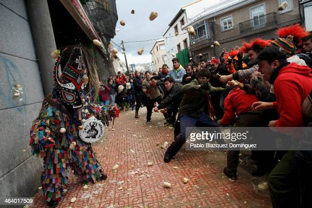 People throw turnips at the Jarramplas as he makes his way through the streets beating his drum during the Jarramplas Festival on January 19 2014 in...
