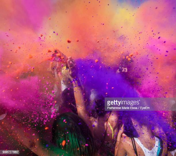 people throwing colorful powder paint during holi festival - holi stock pictures, royalty-free photos & images