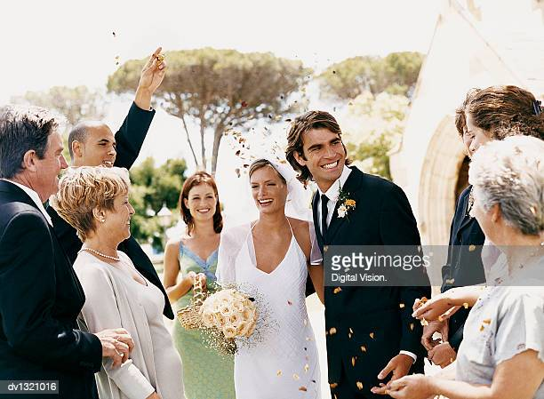 people throwing confetti over a newlywed couple leaving church - church wedding decorations stock pictures, royalty-free photos & images