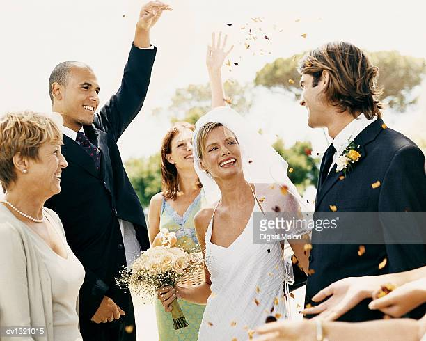 People Throwing Confetti Over a Newlywed Couple