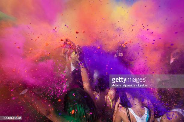 people throwing powder paint during holi celebration - throwing stock pictures, royalty-free photos & images