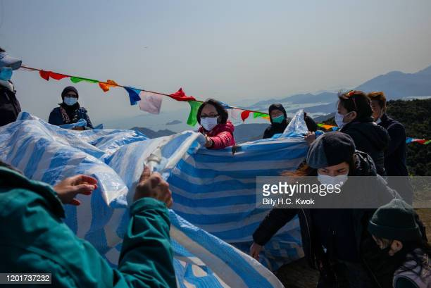 People tidy up after the ninth Hong Kong Buddha Sunning Festival at the Tai Mo Shan lookout on February 18 2020 in Hong Kong China The global death...
