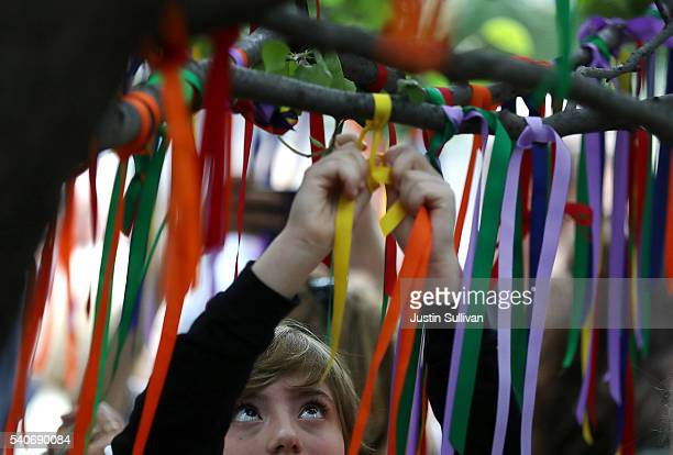 People tie ribbons on the Survivor Tree at the National September 11 Memorial Museum in honor of the victims of the Orlando nightclub attack on June...