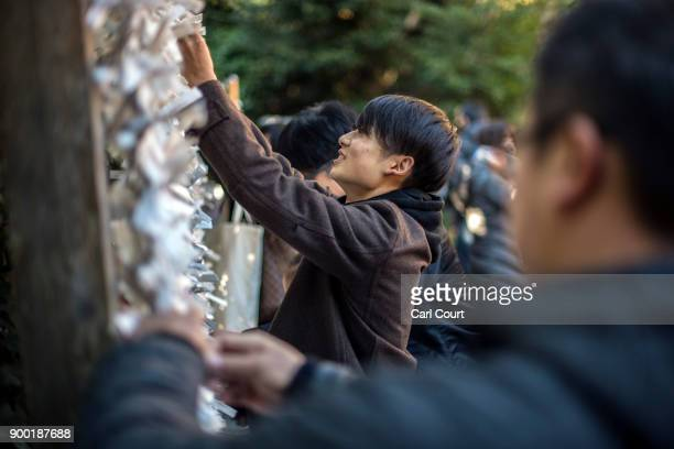People tie their 'omikuji' fortunetelling paper strips after praying for the new year at Tsurugaoka Hachimangu Shinto shrine on January 1 2018 in...