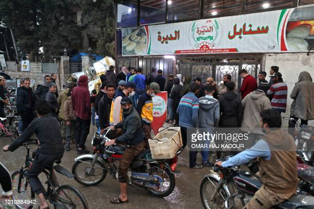 People tightly queue up without masks as they gather outside a bakery in Syria's northwestern city of Idlib on April 24 on the first day of the...