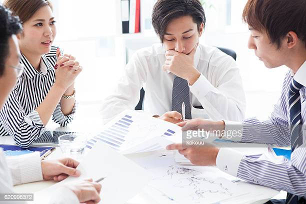People to a meeting while looking at  graph at office