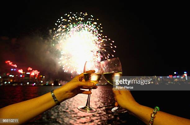 People toast their wine glasses as the annual New Year's Eve fireworks display illuminates the sky over Sydney Harbour on December 31 2009 in Sydney...