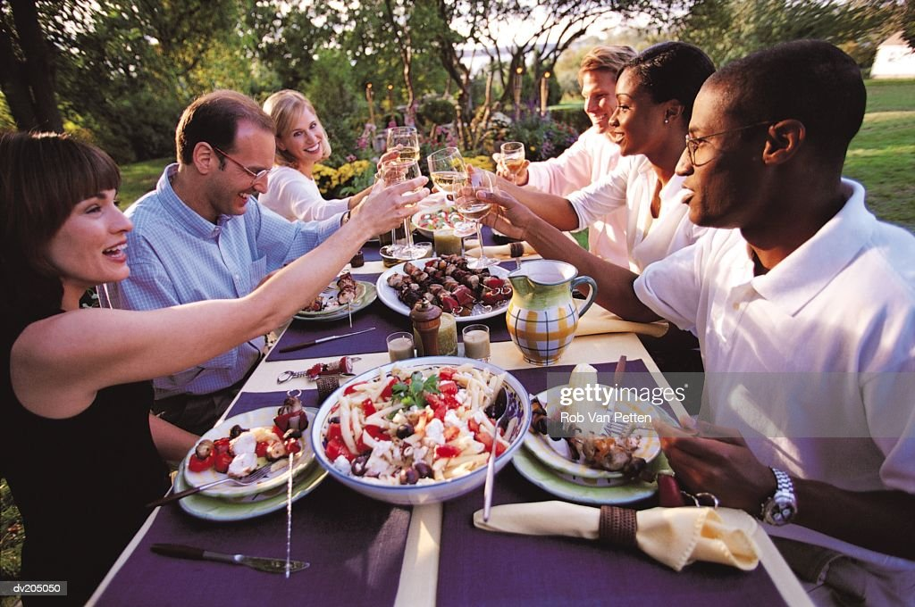 People toasting at an outside dinner party : Stock Photo