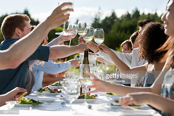 people toasting wine glasses at outdoor dinner party - white wine stock pictures, royalty-free photos & images