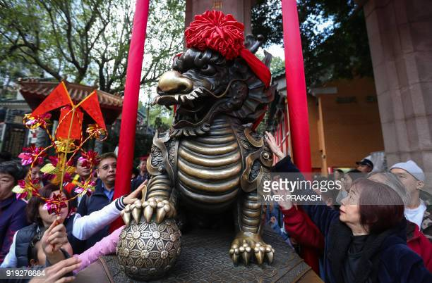 People touch a statue of a lion for good luck as they leave the Wong Tai Sin temple during Lunar New Year celebrations for the Year of the Dog in...