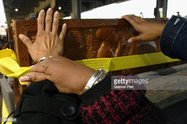 People touch hand-made caskets from Ghana October 3, 2003 containing the remains of former African slaves on route to an African burial ground in New...