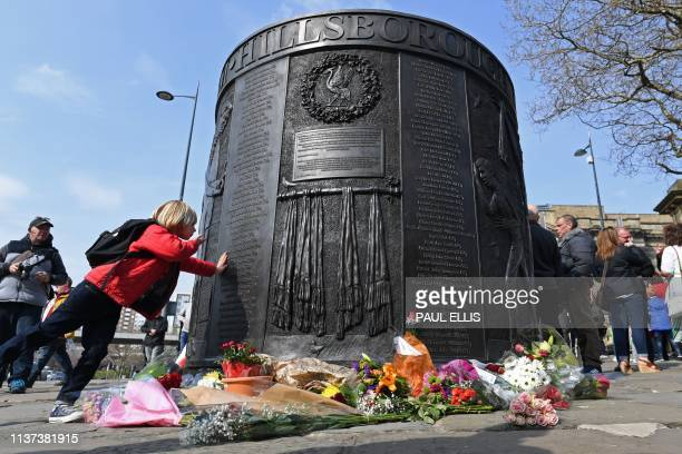 People touch the Hillsborough Memorial Monument where the names of the victims have been written in perpetuity as the city observes a minute's...