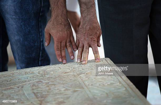 People touch the tomb of beloved Iranian poet Hafez on May 29 2014 in Shiraz Iran Thousands of Muslim pilgrims visit to pray at the shrine one of the...