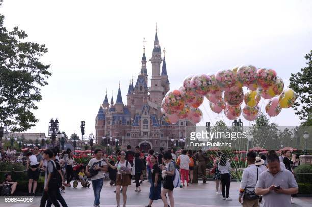 People tour in the Shanghai Disney Resort on June 16 2017 in Shanghai China The theme park received over 11 million visitors in its first year beyond...