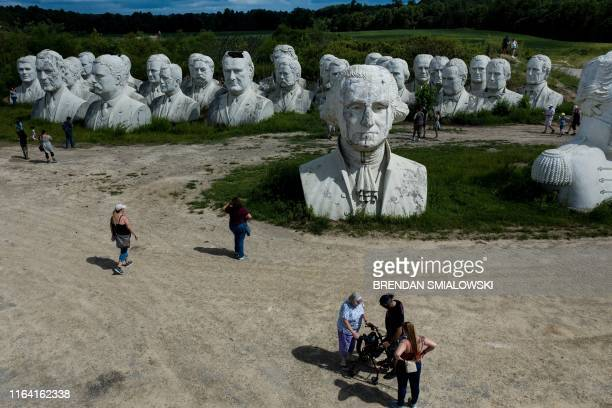 People tour the decaying remains of salvaged busts of former US Presidents August 25 in Williamsburg Virginia Howard Hankins rescued the giant busts...