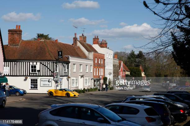 people, tourists and yellow lamborghini visiting the village of dedham - mark dyball stock photos and pictures