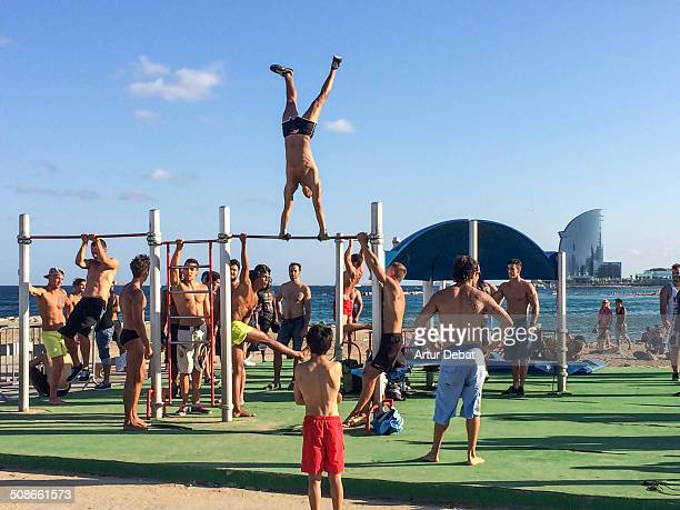 People training his body in the outdoor gym in the beach of Barceloneta in Barcelona's city with the Hotel W on the background