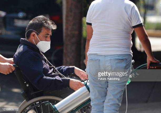 People transport a person with symptoms of possible COVID19 infection to enter at the Naples clinic amid the new virus pandemic on May 27 2020 in...
