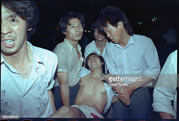 People transport a wounded man during the military crackdown in Tiananmen Square in June 1989