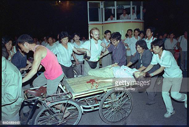 People transport a wounded woman during the military crackdown in Tiananmen Square in June 1989