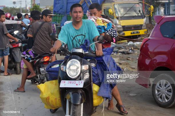People transport looted goods from the Palu Grand Mall in Palu Indonesia's Central Sulawesi on September 30 following the September 28 earthquake and...