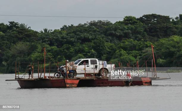 People transport their car in a ferry crossing the Magdalena river in Santa Cruz de Mompox Department of Bolivar September 23 2017 the Colombian town...