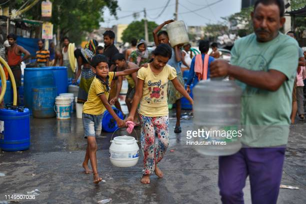 People transport water containers after filling them from a Delhi Jal Board tanker, at Sanjay Colony in Okhla Phase II, on June 12, 2019 in New...