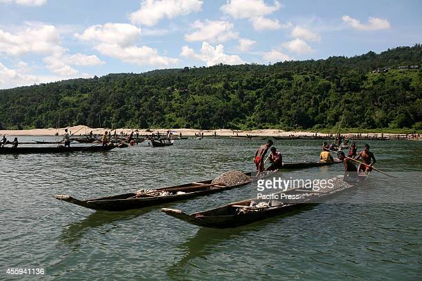 People transporting their collected stones to the nearby local stone businessmen at Piain River Stone collection from underwater during summer is one...