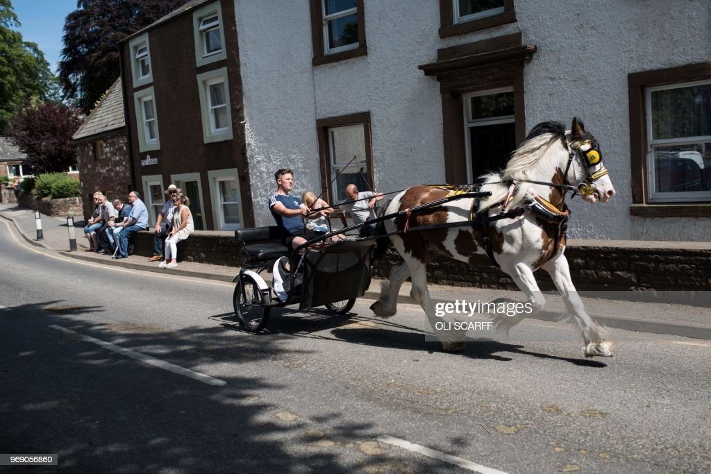 People travel along The Sands street by horse and trap on