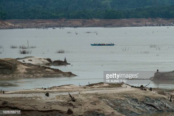 People travel on a boat over decreased level of water after the spillway of Swar Chaung dam collapsed at Swar township Bago region on August 30 2018...