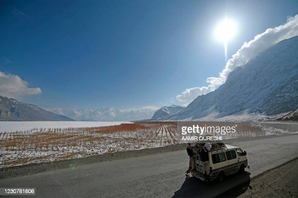 People travel on a passenger van in a snow-covered area on the outskirts of Skardu on January 24, 2021.
